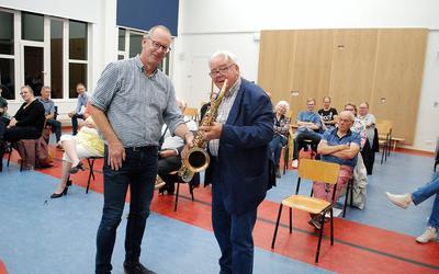 Voorzitter Lambert Vos (l) neemt de saxofoon van Jan Tijink in ontvangst.