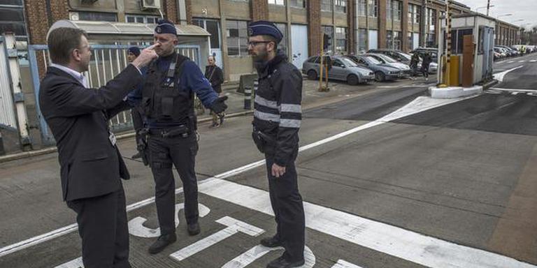 Een politieagent geeft aanwijzingen aan reizigers bij luchthaven Brussel. FOTO ANP/JONAS ROOSENS