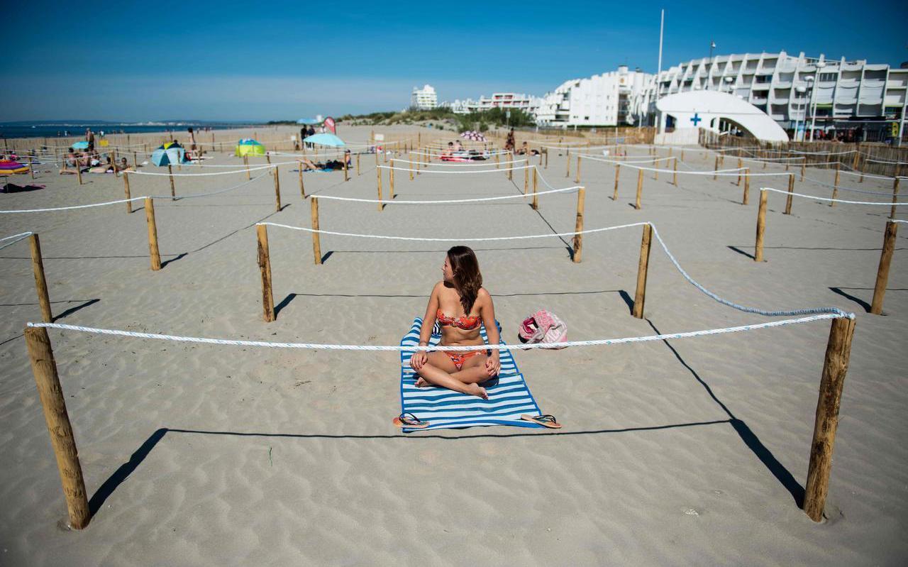 Op het strand van La Grande Motte, in het zuiden van Frankrijk, is duidelijk aangegeven hoeveel afstand bezoekers van elkaar moeten houden.
