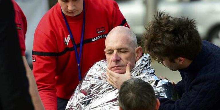 Een slachtoffer wordt behandeld aan de verwondingen die hij opliep bij de aanslag op metrostation Maalbeek. FOTO AFP/EMMANUEL DUNAND