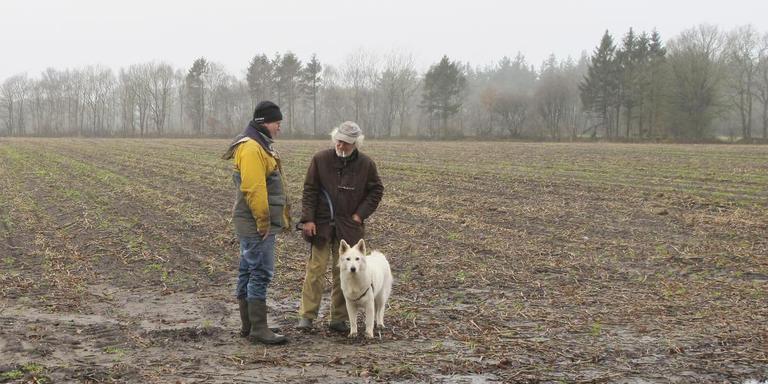 De Zwitserse witte herder Tara met zijn baasje Henk Paas (rechts) en archeoloog Marcel Niekus. Foto: Gijsbert Boekschoten