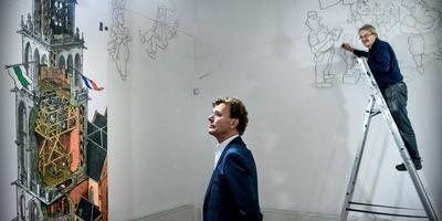 Directeur Victor Boswijk en op de trap Frans Le Roux, die werkt aan zijn afsluitende expositie in het Nederlands Stripmuseum aan de Westerhaven