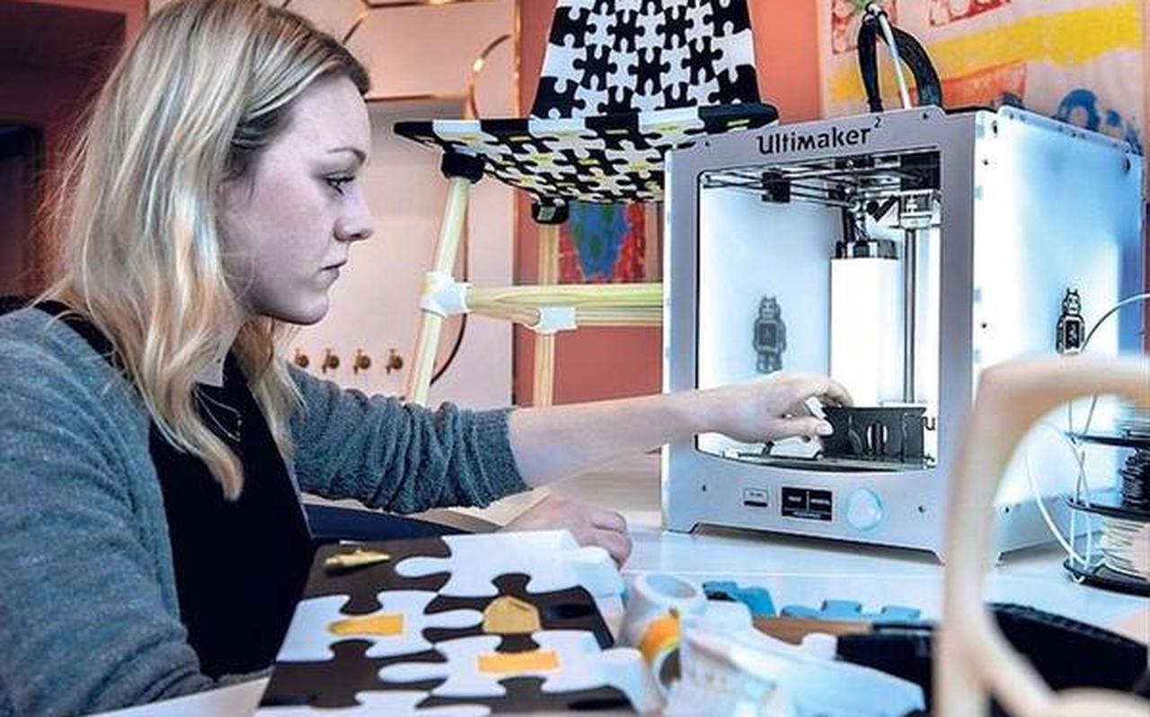 Wietske van der Graaf is bezig met de 3D-printer met op de achtergrond de stoel, het eindresultaat. FOTO PETER WASSING