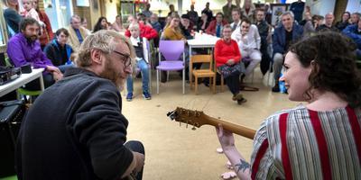 Anne Ceasar van Wieren en Eva Waterbolk brengen enkele liederen ten gehore tijdens de presentatie van de dichtbundel van Kasper Peters (links).