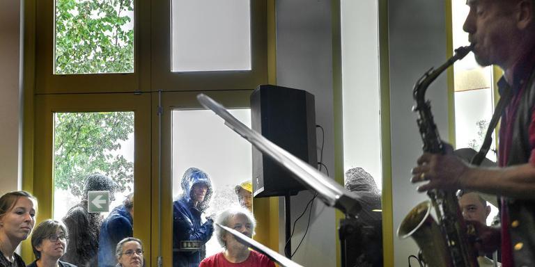 Tijdens het optreden van De Commotie in Museum Wierdenland trotseert publiek een plensbui. foto peter wassing