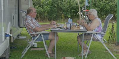 Egbert en Jannie Wildeboer genieten een ontbijtje bij hun camper.