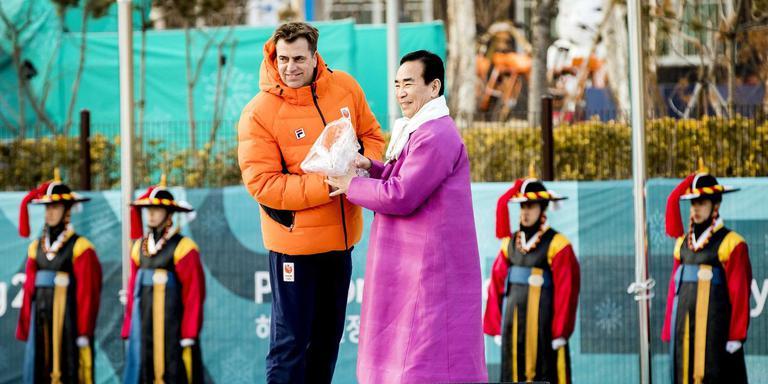 Chef de mission Jeroen Bijl overhandigt een Oranjevaas aan de tijdelijke burgemeester van het olympisch dorp, Kim Ki-Hoon. Foto: ANP