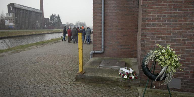 De krans en de bloemen worden voorafgaand aan de herdenking nog even uit het zicht gehouden, tegen de gevel van de oude strokartonfabriek aan. Op de achtergrond de restanten van de aardappelmeelfabriek. Foto Jan Anninga
