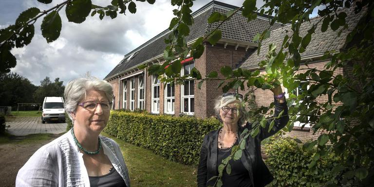 Omwonenden Annemarie Machielsen (links) en Jolanda van den Bosch bij het schoolgebouw en het terrein dat vol moet komen te staan met nieuwbouw.
