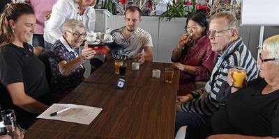 Dobbelen met eenzame ouderen. FC Emmen-voetballer Stef Gronsveld (midden) doet mee. FOTO BOUDEWIJN BENTING