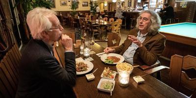 Hein Klompmaker (links) en Dirk Mulder aan de schnitzel in hun gezamenlijke stamcafé Hofsteenge in Grolloo. Foto: Jaspar Moulijn