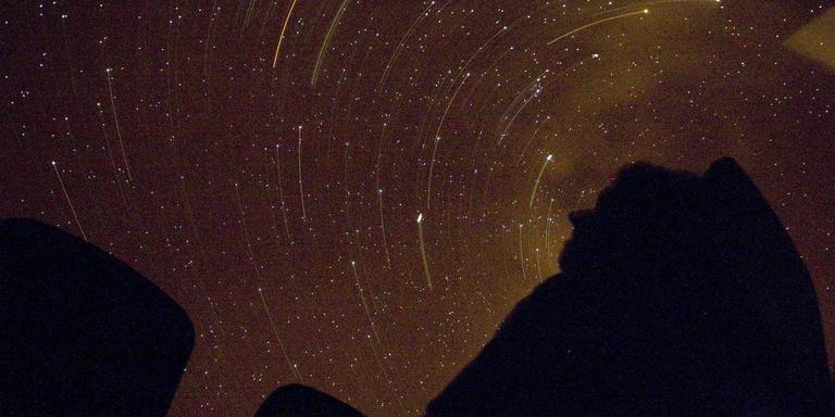 In het Planetron in Dwingeloo kijken bezoekers door een telescoop naar vallende sterren. FOTO ANP/DENNIS BEEK