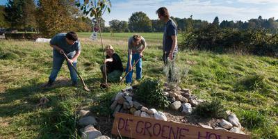 Steven en Mike planten samen met begeleidster Andrea een kersenboom, Gertjan Drenth kijkt toe. Foto Gerrit Boer