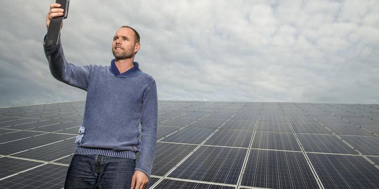 Jan Reinier de Jong bij de zonnepanelen op zijn bedrijf.