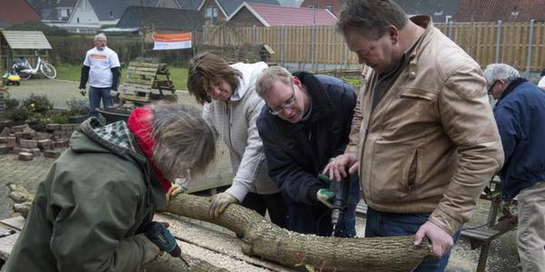 Bewoners van Visio De Brink boren gaatjes voor de paddenstoelenkweekplek vorig jaar tijdens NL Doet. FOTO HILBRAND DIJKHUIZEN