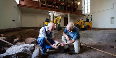 Archeologen Gertjan de Roller van ingenieursbureau MUG en Pieter den Hengst aan het werk in de Stefanuskerk. Links naast hen een rij veldkeien, die mogelijk duiden op oude fundering. Foto Gerrit Boer.
