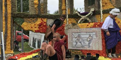 Figuranten op 'De Romeinse Spelen' zijn blij dat ze de middagparade er op hebben zitten. Zaterdagavond kreeg deze wagen de eerste prijs. Foto DvhN