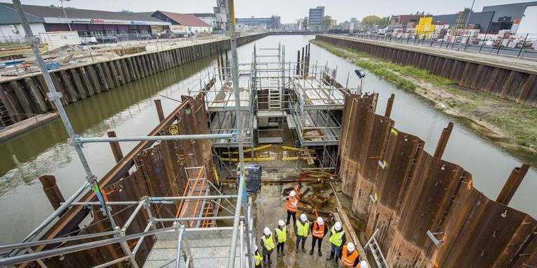Raadsleden en andere geinteresseerden nemen een kijkje op de bodem van de nieuwe Sluis 2 in het Havenkanaal. Links de Havenkade, op de achtergrond de Blauwe Klap. FOTO MARCEL JURIAN DE JONG