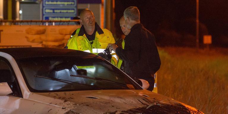 Agenten inspecteren de gestolen auto nadat de bestuurder was gearresteerd. Foto: Archief De Vries Media
