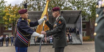 Commandant Gert Strick (rechts) neemt het vaandel voor de overdracht in ontvangst. Foto: Defensie/Tim van Rijt