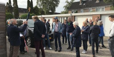 Tony van der Lee (met paraplu) geeft de raadsleden van Noordenveld en andere belangstellenden uitleg over de schade in de wijk. Foto DvhN