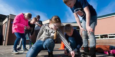 Leerlingen van obs De Posthoorn in Pesse krijgen rekenles op het schoolplein en ze zijn daarbij veel in beweging. Foto: Gerrit Boer
