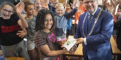 Loco-burgemeester van Coevorden Jeroen Huizing zet nationaal voorleeskampioene Yosan Wegihu Teame (11) in het zonnetje en beloont haar met een boekenbon. Haar klasgenoten van cbs De Fontein in Sleen juichen mee.