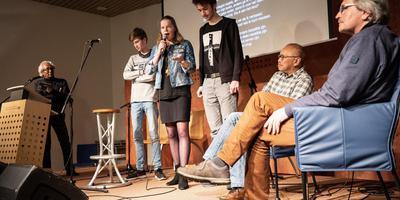 Leerlingen van het Harens Lyceum zingen in Herinneringscentrum Kamp Westerbork hun lied De Brug over gegijzelde Bernhard Hanskamp (rechts) en Molukker Pieter Anthony (tweede van rechts). Links Noes Solisa. Foto Jaspar Moulijn