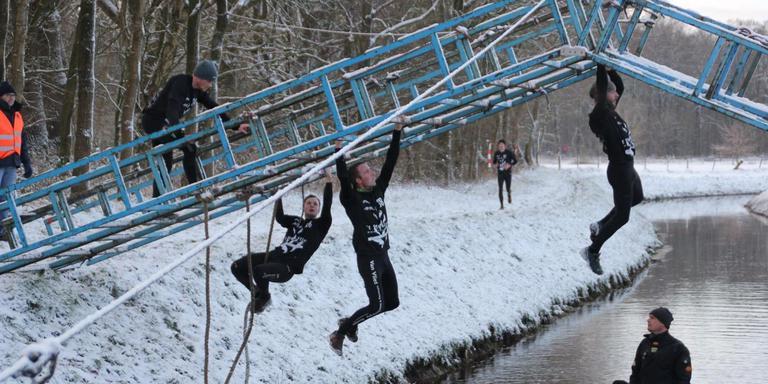 Deelnemers van een vorige editie nemen één van de hindernissen.