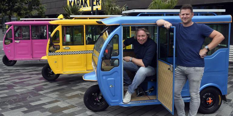Henk Eising en Adriaan van Leeuwen (rechts) met hun tuktuk voor café Karakter op het Raadhuisplein. FOTO HENK BENTING