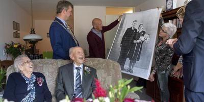 Het echtpaar Zwiggelaar, met hun trouwakte in de hand, kijkt vrolijk toe hoe wanneer hun kinderen de uitvergrote trouwfoto uit 1943 laten zien.