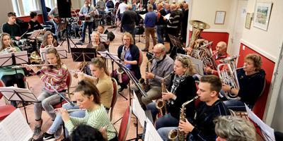 Drukke repetitie in dorpshuis De Pan. Harmonie Vries op de voorgrond, Joint Venture en het Mannenkoor op de achtergrond. Foto Harry Tielman