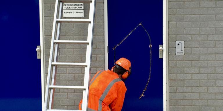 Een medewerker van de brandweer zaagt een gat in de deur om Corrie Hendrikx te bevrijden. Foto: DvhN