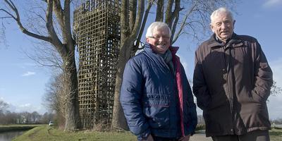 Riekus Holties (rechts) en Lucas Schoemakers bij de toren waarop zij zelf werkzaam waren. De bomen zijn inmiddels verdwenen. Foto: Archief Jan Anninga