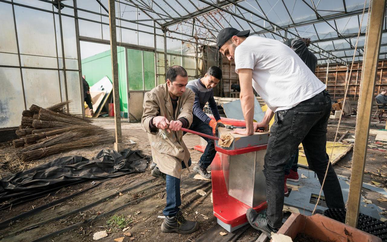 Vrijwilligers van het Alfa-college slopen meubels die niet meer gebruikt kunnen worden. Foto Jaspar Moulijn