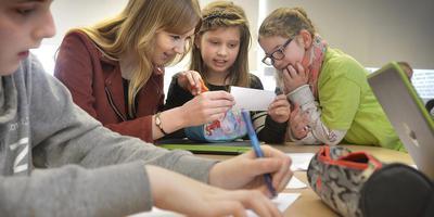 Dian Poppen helpt de kinderen met hun meertalige gedicht. Foto: Jan Anninga
