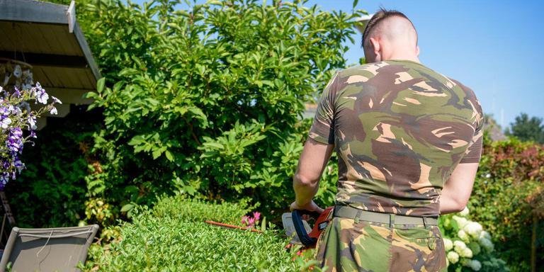 Staat er ineens een militair de heg te snoeien. Foto The Colony