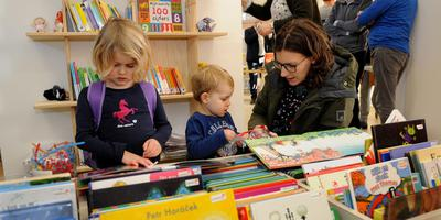 Julia en Teun duiken met hun moeder meteen in de boeken. Foto Henk Benting