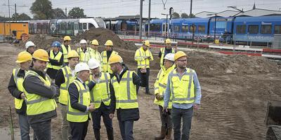 Gedeputeerde Henk Brink (voorgrond links, met witte helm) laat zich bijpraten over de werkzaamheden rond het treinstation in Coevorden. Wethouder Jeroen Huizing (naast Brink, eveneens met witte helm) luistert mee. Foto Jan Anninga