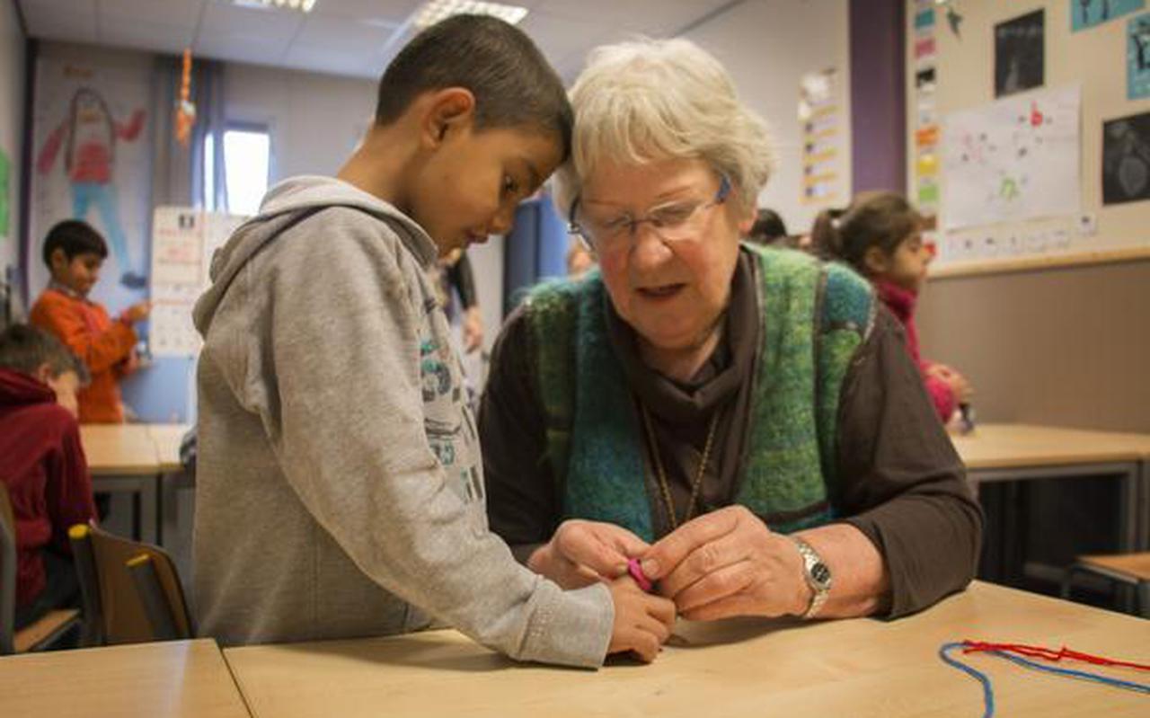 Een leerling van de asielschool leert van een vrijwilligster van het Interkerkelijk Platform Oranje hoe je een vriendschapsbandje maakt. FOTO DVHN
