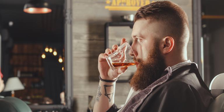 Een drankje in de kappersstoel. Het gebeurt wel, maar het mag officieel niet. Foto: Shutterstock