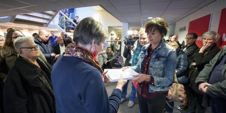 Medewerkers bieden Janny Vlietstra zo'n 1100 handtekeningen aan. FOTO HILBRAND DIJKHUIZEN