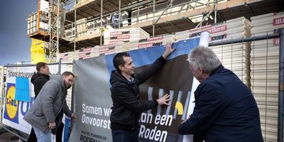 Projectleider Mark Smit, Aldwin Wierstra en Dennis de Jong van Lidl en wethouder Henk Kosters hangen het Bouwhekdoek op. Foto Peter Wassing
