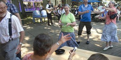 Deelnemers aan de Fiets4Daagse komen al dansend en zingend de stempelpost in Aalden binnen. FOTO JAN ANNINGA