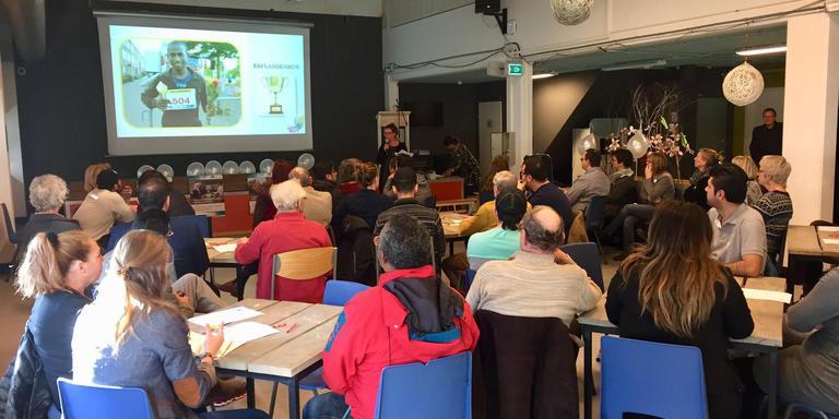 Asielzoekers en vertegenwoordigers van organisaties luisteren naar de presentatie over vrijwilligerswerk in azc Hoogeveen. Foto: DvhN