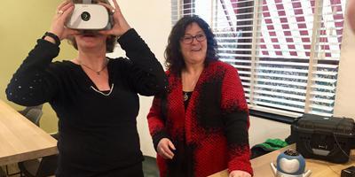Margriet de Boer (rechts) geeft uitleg over VR-iendje, die de beelden doorstuurt naar de speciale bril. Foto: DvhN