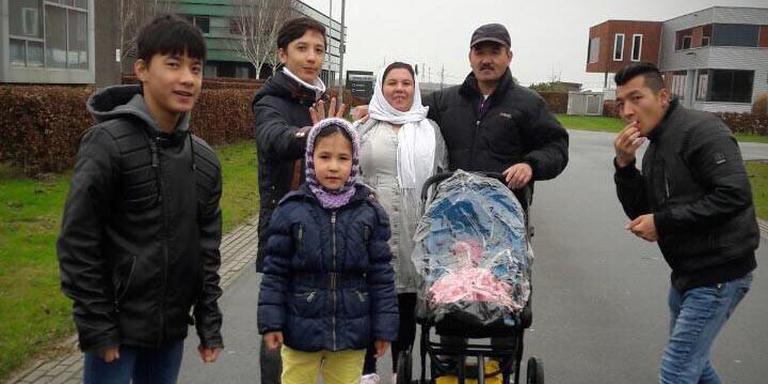 Famili Zafiri: Mohammed (12), Ali (14) en Zara (8) en hun ouders met een kennis en kindje van vrienden in kinderwagen.