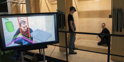 Een voorbeeld van een techniek die in het bedrijfsleven wordt toegepast en waar studenten op het Alfa-college mee leren werken. Met een bril kunnen zij zien of het ontwerp voor een installatie - met een bril virtueel zichtbaar - past in een bepaalde ruimte, in dit geval een box (rechts) in het praktijklokaal. De weergave is ook te zien links op het scherm.