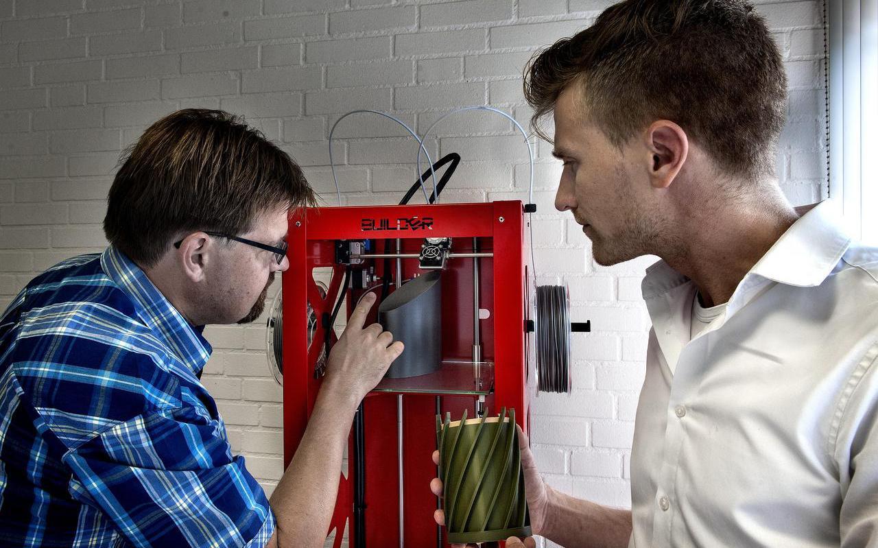 Peter Dijkstra (links) en Martin Tietema bij de 3d-printer die een urn maakt. FOTO PETER WASSING