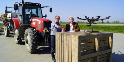 Michiel Bus (links) van SPNA en Luuk Jansen van Dronehub bezegelen de afspraak die Dronehub nieuwe testgebieden oplevert. Foto Merlin van Mil
